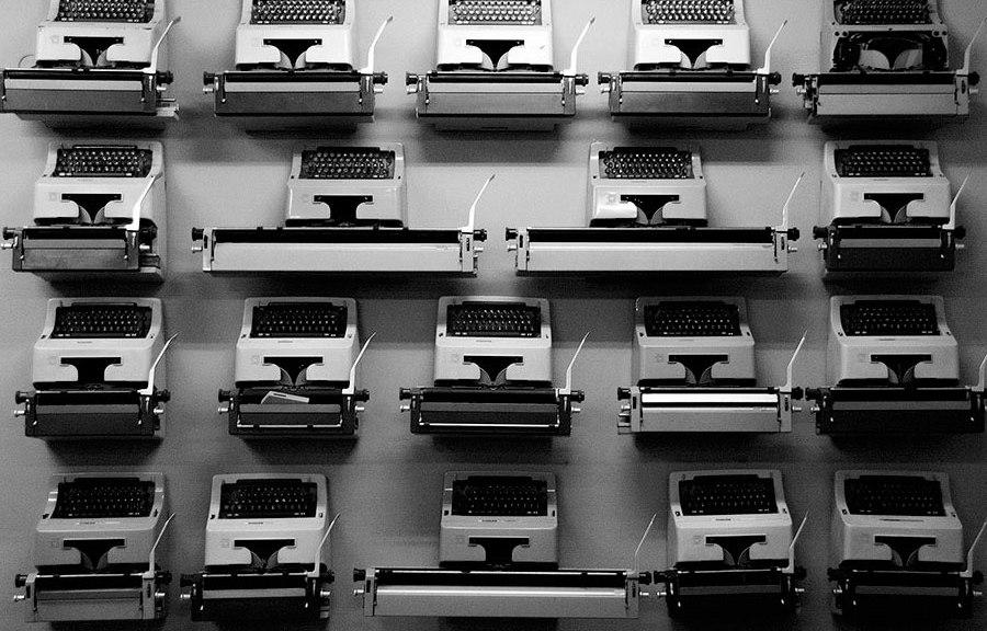 Imagen de una pared en la que hay colgadas máquinas de escribir antiguas